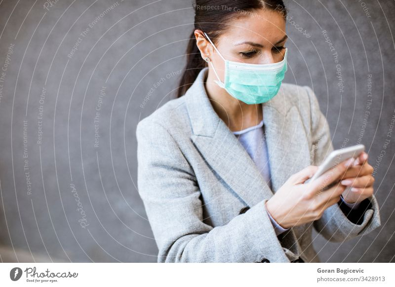 Pretty young woman with protective facial mask on the street virus health contagious safety epidemic phone disease mobile coronavirus pandemic flu medical