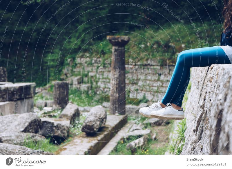 Girl is sitting on remains of a Doric temple, Mon Repos park, Corfu Town, Greece corfu mon greece palace repo repos kerkira island building landmark historic