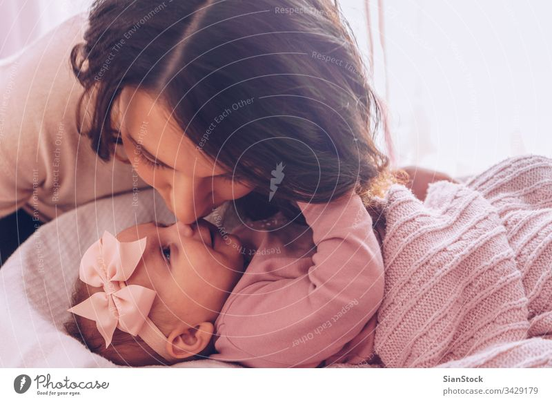 Young mother kissing her adorable baby girl. mom happy family kid child nose playing loving beautiful portrait happiness young love daughter little white cute