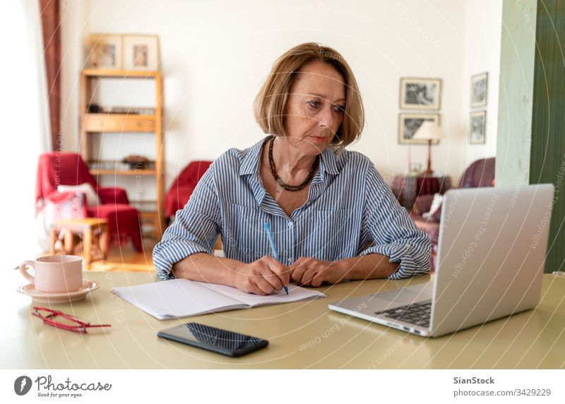 Middle age senior woman working at home using computer female laptop mature people one house person lifestyle desk drink glasses attractive relax technology job