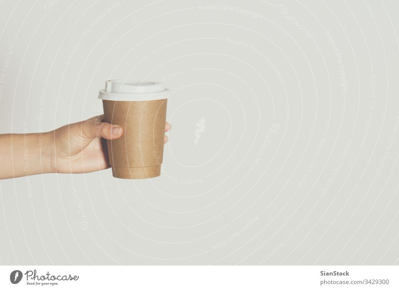 Womans hand holding brown paper cup of hot coffee. isolated white drink woman background disposable cafe lid container caffeine breakfast icon design drinking