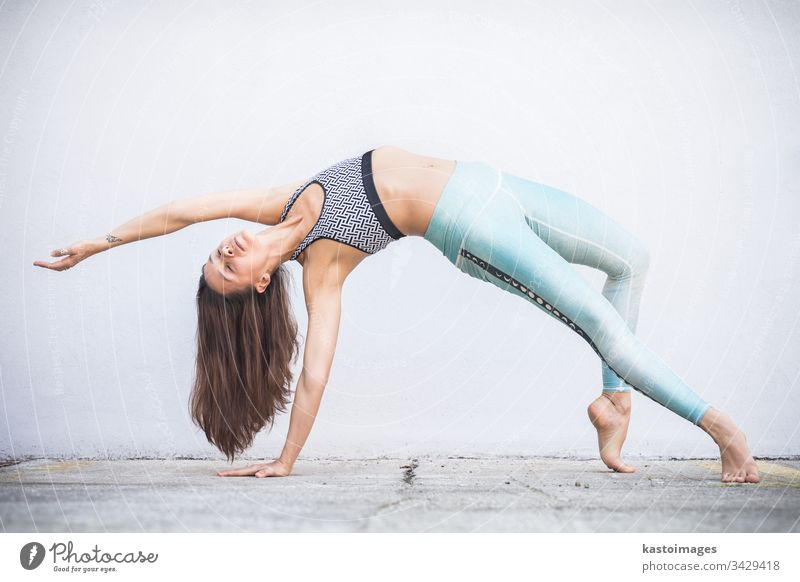 Fit sporty active girl in fashion sportswear doing yoga fitness exercise in front of gray wall, outdoor sports, urban style woman dance gym training slim female
