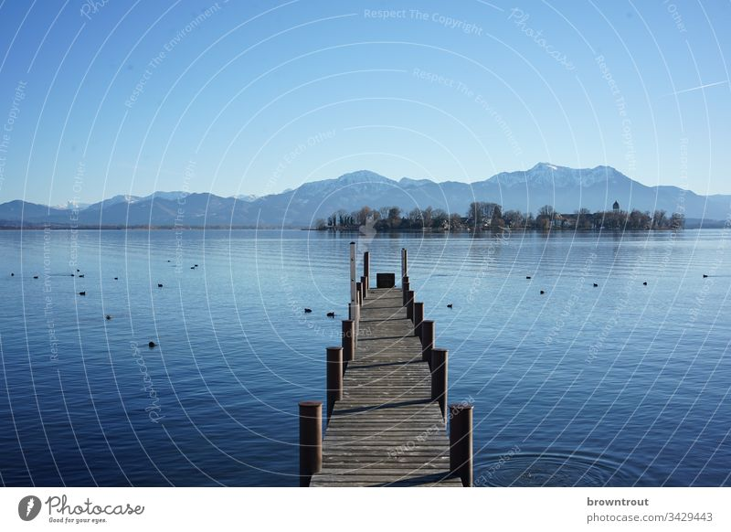 Boat landing stage at the Chiemsee with view of the Fraueninsel. Footbridge Lake Water Wood Blue Alps Island Mountain Blue sky Lake Chiemsee Gstadt