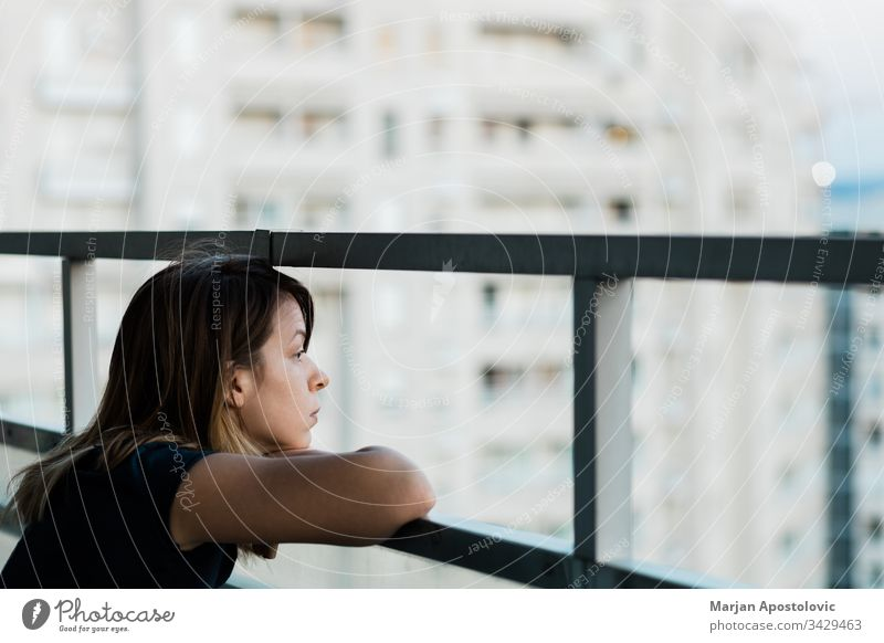 Young sad woman looking outside through balcony of an apartment building adult alone anxiety caucasian city concerned crisis depressed depression desperate