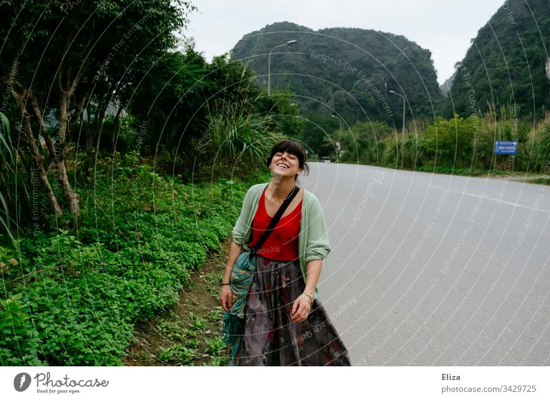 A young woman in colourful clothes walking along an empty street in Asia and smiling Woman variegated tourist Tourism South East Asia Joie de vivre (Vitality)