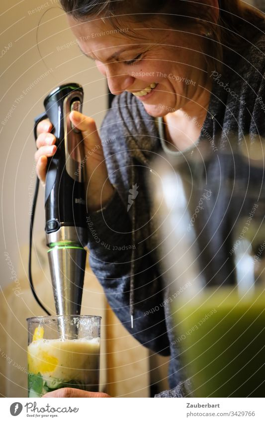 Pretty woman makes a smoothie with the hand blender and smiles Woman pretty already green salubriously Healthy Adults Human being Interior shot cake Glass