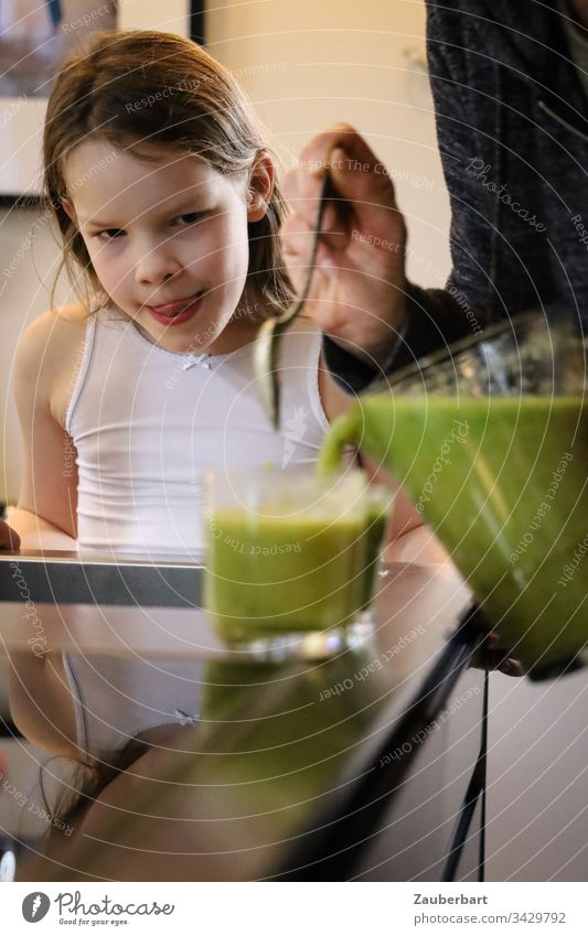 Little girl watches green smoothie being poured into a glass and is looking forward to it Child Infancy Delicious salubriously Beverage Glass Carafe Self-made
