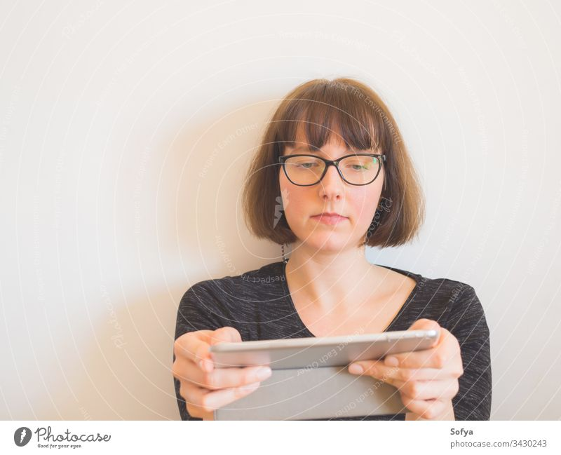 Caucasian woman with glasses using tablet gadget sitting caucasian portrait middle work home quarantine bob horizontal aged internet room technology copy space