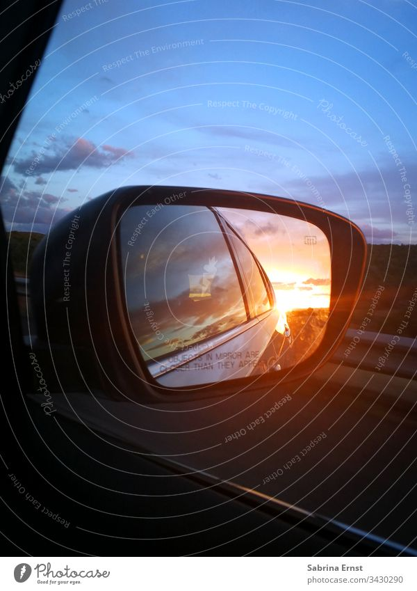 Reflection of a sunset in the exterior mirror car mirrors Car Sunset colourful Light Transport Street Highway travel road trip Review panorama Landscape