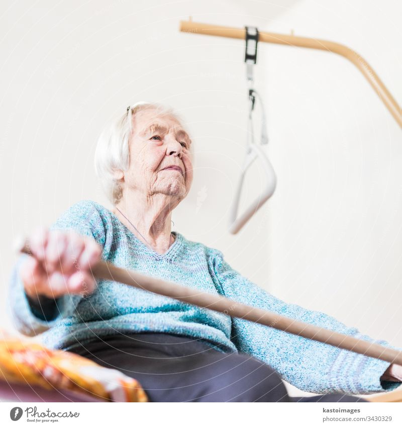 Elderly 96 years old woman exercising with a stick sitting on her bad. health care senior geriatric workout home bed patient happy social pensioner retirement