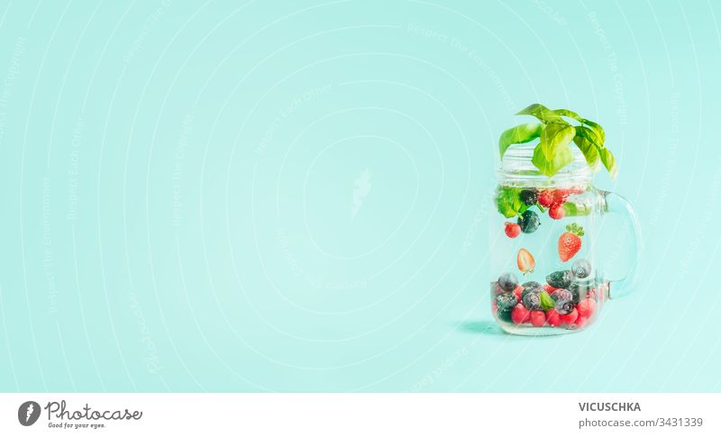 Berries detox fruit infused water in Mason jar flavored with herb leaves on table  at sunny turquoise blue background. Summer mood drinks and lifestyle. Healthy background
