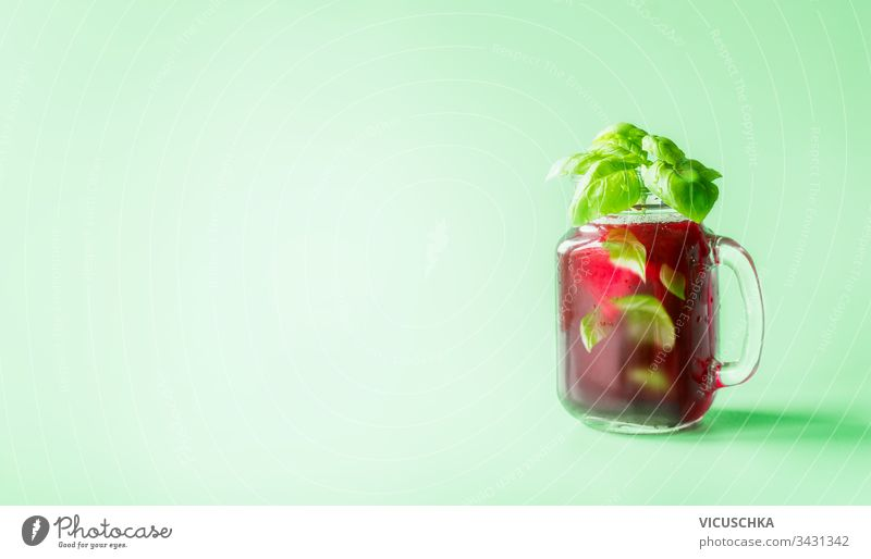 Red berries lemonade in Mason jar  flavored with herb leaves at sunny bight mint green background. Summer mood.  Healthy drinks and lifestyle. Copy space