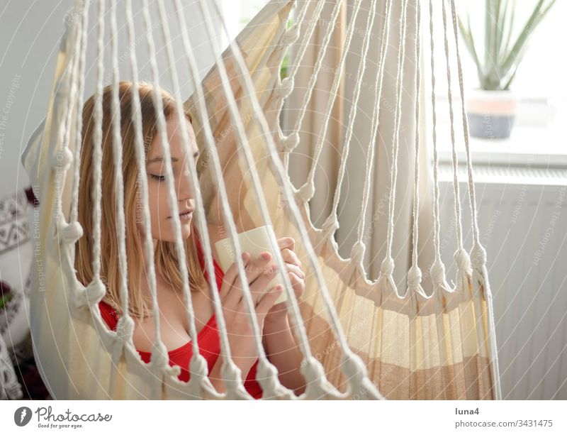 young woman with cup in hammock Woman Hammock Cup Dreamily room Coffee melancholically Tea Drinking Beverage Meditative Coffee cup food Smiling sensual To enjoy