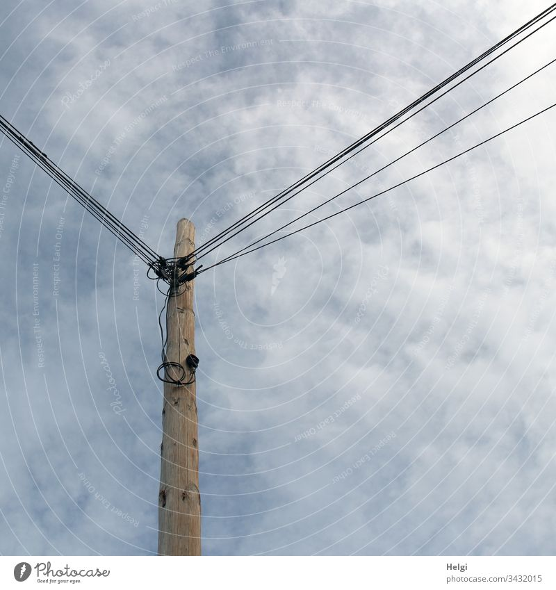 high wooden mast with many attached power lines in front of a cloudy sky Pole Electricity pylon Cable Energy industry electricity Transmission lines Technology