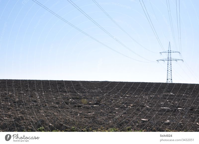 High voltage pylon stands lonely at a distance on a ploughed field Electricity pylon stream power supply acre Plowed Agriculture Horizon Winter Lonely