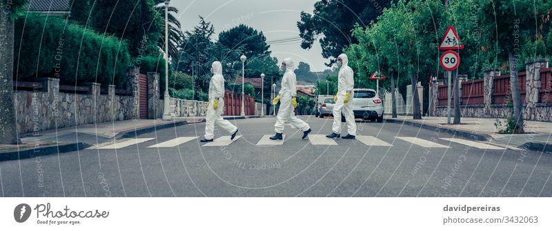 People in bacteriological protection suits walking down an empty street covid-19 coronavirus curfew quarantine crosswalk pandemic epidemic outdoor banner web
