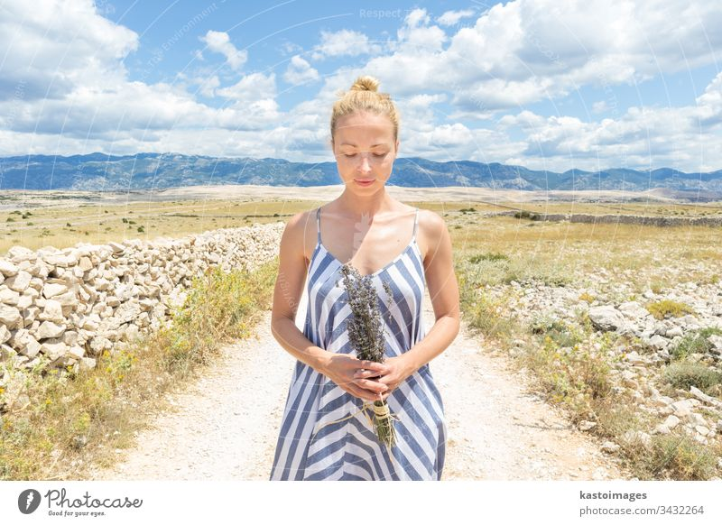 Caucasian young woman in summer dress holding bouquet of lavender flowers enjoying pure Mediterranean nature at rocky Croatian coast lanscape on Pag island in summertime