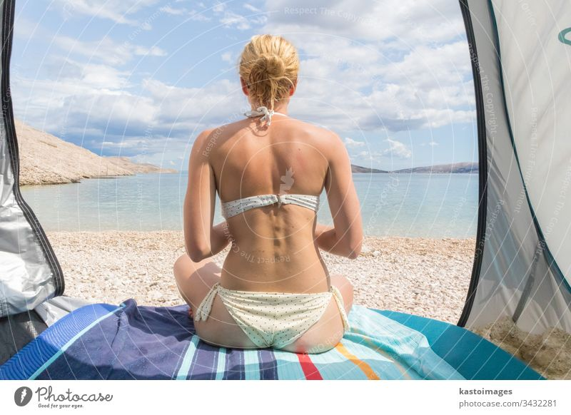Rear view of beautiful young caucasian woman enjoying summer sun on Mediterranean beach protected from heat and sunburns by shade tent. beauty lifestyle ocean