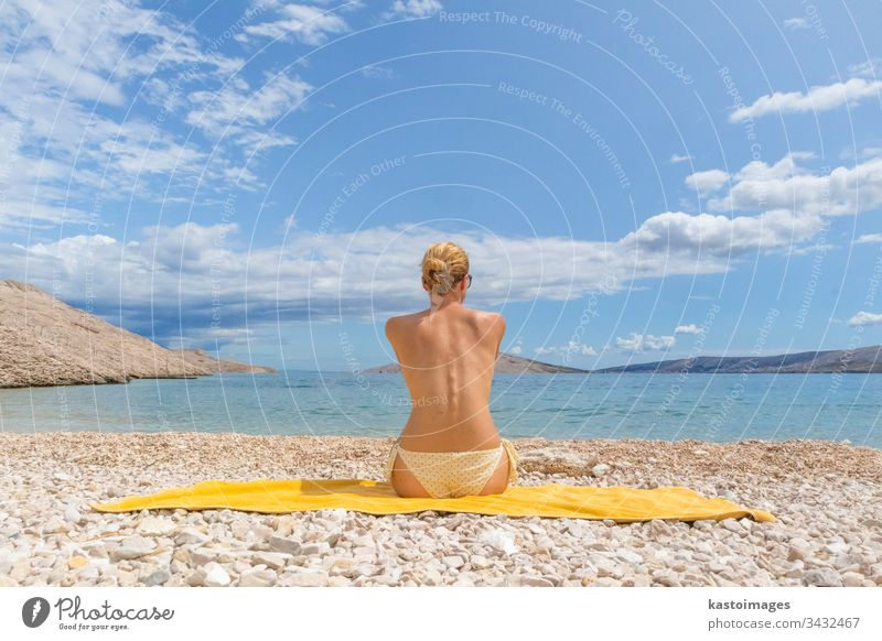 Rear view of sexy young caucasian woman sunbathing topless on romote pabble beach on Pag island, Croatia, Mediterranean. summer body tanning vacations beauty