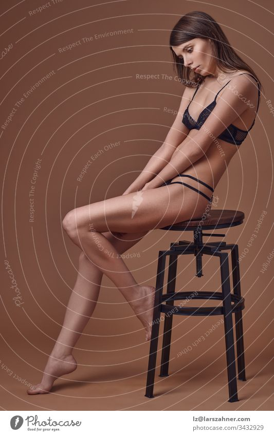 Sexy slim young woman seated elegantly on a stool in her black lingerie in a side view portrait on brown as she looks demurely down at her hands clasped between her bare legs with copy space