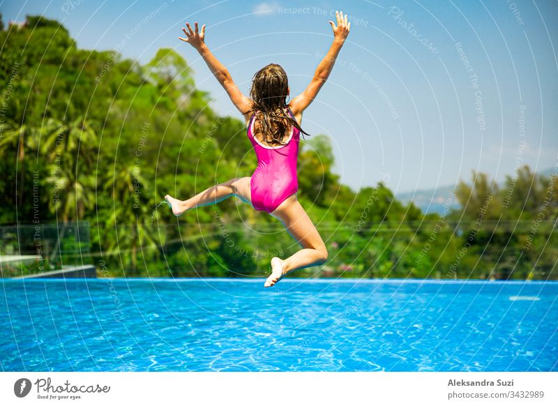 Excited funny little girl jumping to the swimming pool. Happy summer vacation active adventure asia blue candid carefree cheerful child childhood colorful crazy