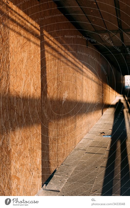 long shadow of a person on the sidewalk Shadow Corridor off Construction site Wood Mysterious Protective gloves Tunnel Tunnel vision Scaffolding