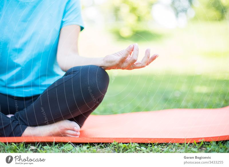 Senior woman in a lotus position   on a grass senior park health exercise beautiful yoga mature person fit female outdoors elderly adult people fitness nature
