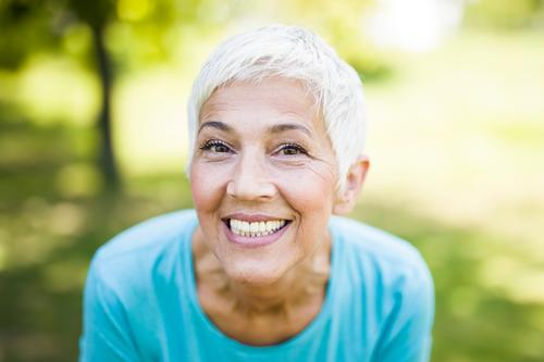 Portrait of a smiling sporty senior woman in a park smile female caucasian portrait person healthy fitness active happy gray lifestyle hair elderly outside