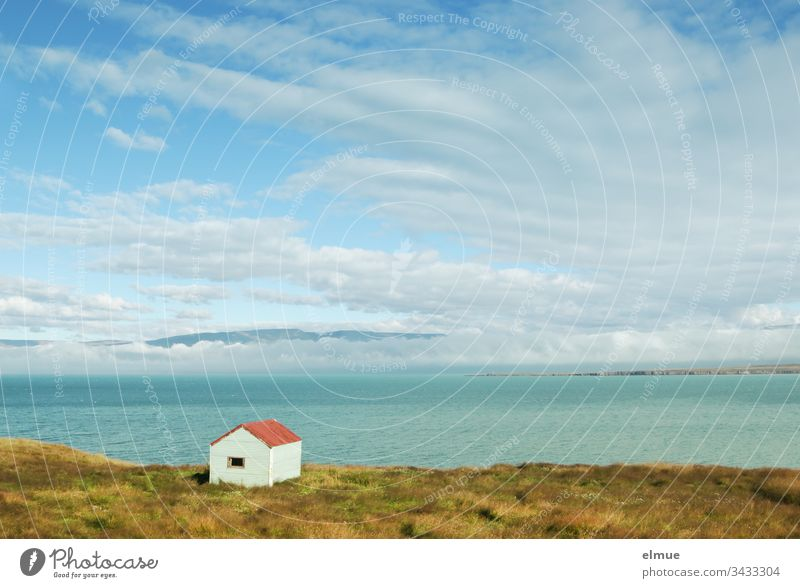 small hut on the shore and view over the water to cloudy mountains (Iceland) Hut Water bank Reykir Lonely Loneliness Exterior shot Nature