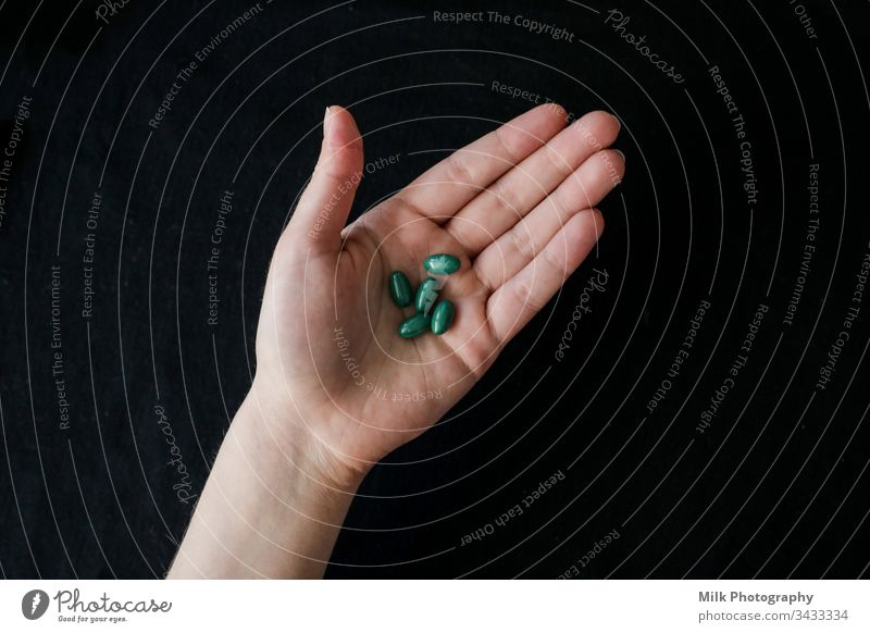 Bright green pills in a human hand Close-up painkillers assorted antibiotic Vitamin supplement remedy prescription Pill Pharmacy paracetamol medicines Headache