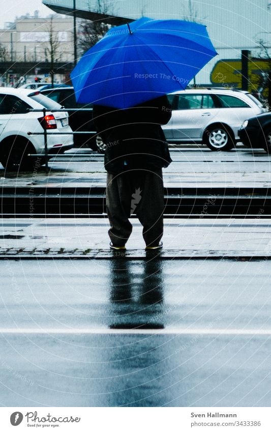 Man with blue umbrella is waiting Blue Umbrella baggy Stop (public transport) cars Wait Human being Rain Adults Bad weather Colour photo Weather Exterior shot