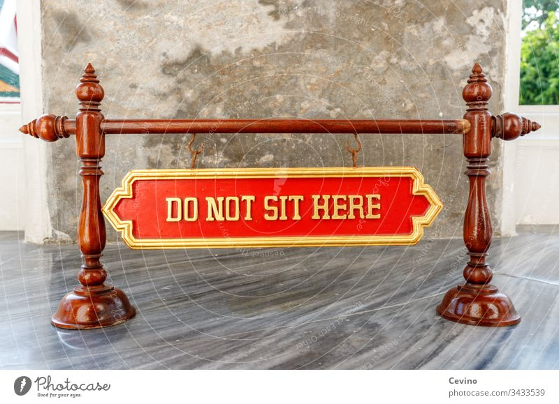 Sign Do not sit here sign Warn Assignment interdiction dunning Temple Buddha Buddhism Buddhist religion Belief Superstition red background Gold Marble floor
