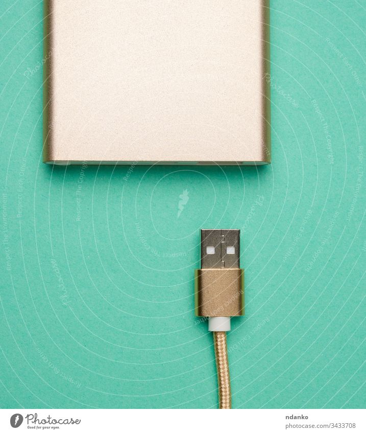 golden power bank and cord with a usb connector for recharging mobile devices on a green background cable charger energy technology battery digital plug
