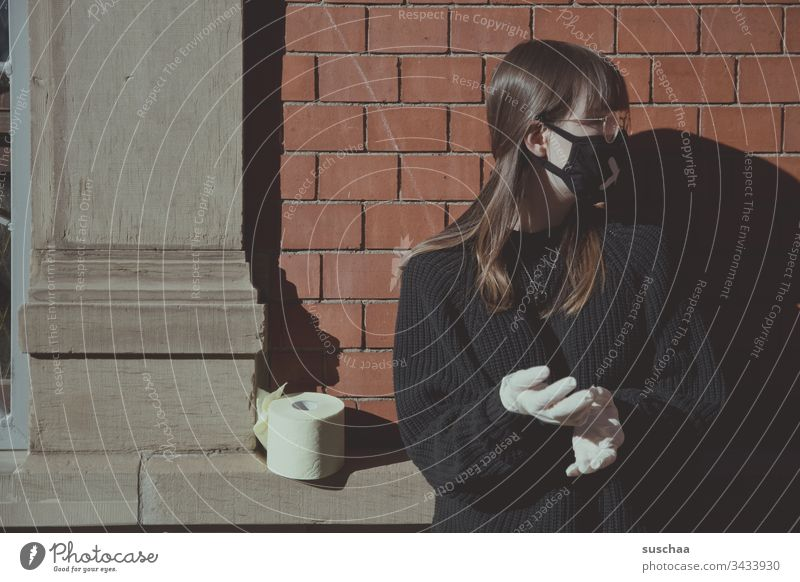 teenager with face mask on a house wall with toilet paper | corona thoughts Youth (Young adults) Young woman at home home office Eyeglasses stay at home Crisis