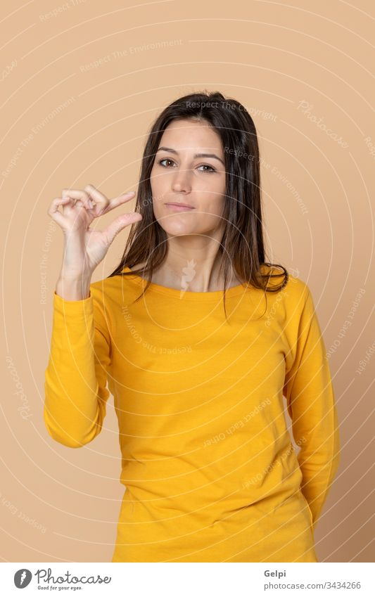 Attractive young girl wearing a yellow T-shirt person bit little illness indicate indicating finger advertisement copy space expression gesture beautiful female