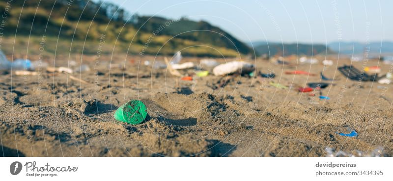 Dirty beach landscape full of waste trash garbage plastic sand dirty contaminated environment nature pollution banner web panorama panoramic coast plastic lid
