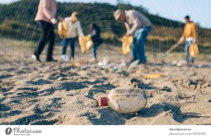 Volunteers cleaning the beach plastic bottle family volunteering dirty garbage bags ecological conscience group tools environment child people male collect