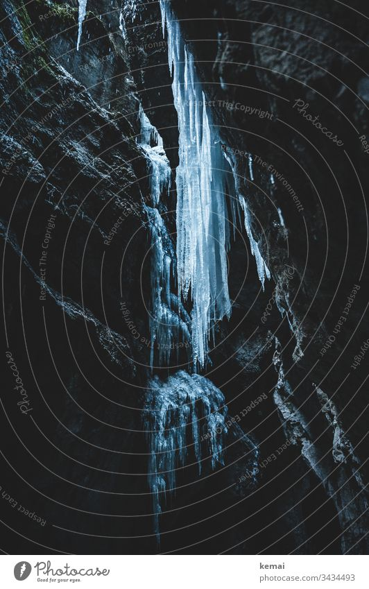Icicle in canyon Winter Cold Ice Canyon rock Dark somber icily Hang Stone Large gigantic clammy Nature natural beauty Frozen Water Blue
