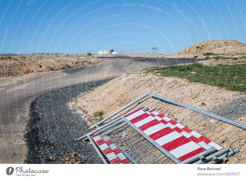 View into a building area Development area Construction site Stationary red and white cordon Protective Grating curvaceous Street fallow Blue sky