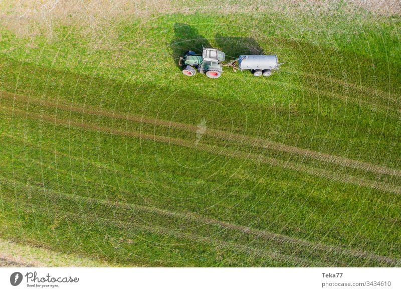 tractor spraying cow dung from above #3 farming tractor agriculture agricultural meadow field grass modern modern agriculture modern machine farming machine