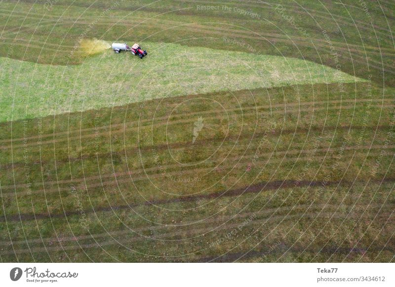 tractor spraying cow dung from above #2 farming tractor agriculture agricultural meadow field grass modern modern agriculture modern machine farming machine