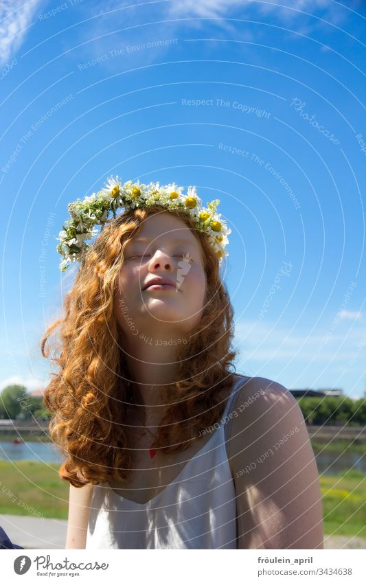 redheaded woman with wreath of flowers in her hair Flower wreath Sun relaxation Margariths tranquillity Summer daylight To enjoy Young woman