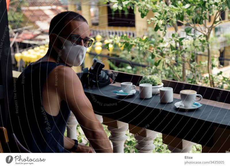 A man with a face mask is sitting in a café abroad, where he is stranded because of the corona virus COVID covid-19 Foreign countries Man Tourist Life vacation