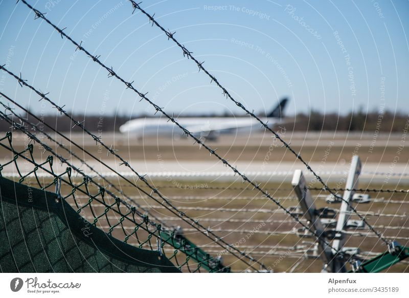spiked fence with a blurred plane parked behind it Airplane Barbed wire fence Fence Exterior shot Airport Safety Border Barrier Deserted Colour photo Protection