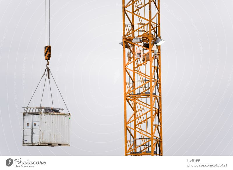 Aluminium ladder on floating container on the load hook of a crane Construction site Crane Ladder construction site supply Work and employment Craft (trade)