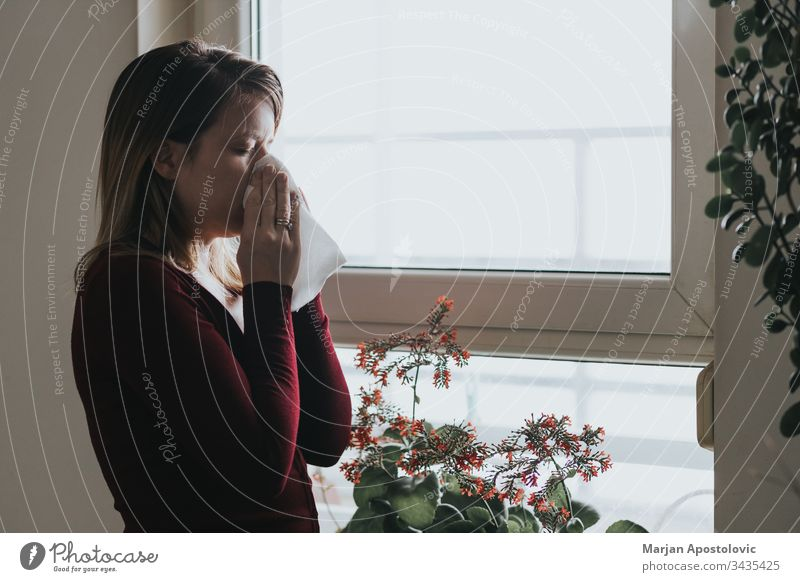Young sick woman blowing her nose into a handkerchief by the window 30s adult allergy alone apartment care casual caucasian cold contagion dark disease epidemic