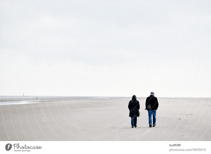 Walking on the beach in winter couple Beach Sand Sandy beach Couple North Sea coast Mud flats Vacation & Travel Island shallow water Coast Horizon Surf