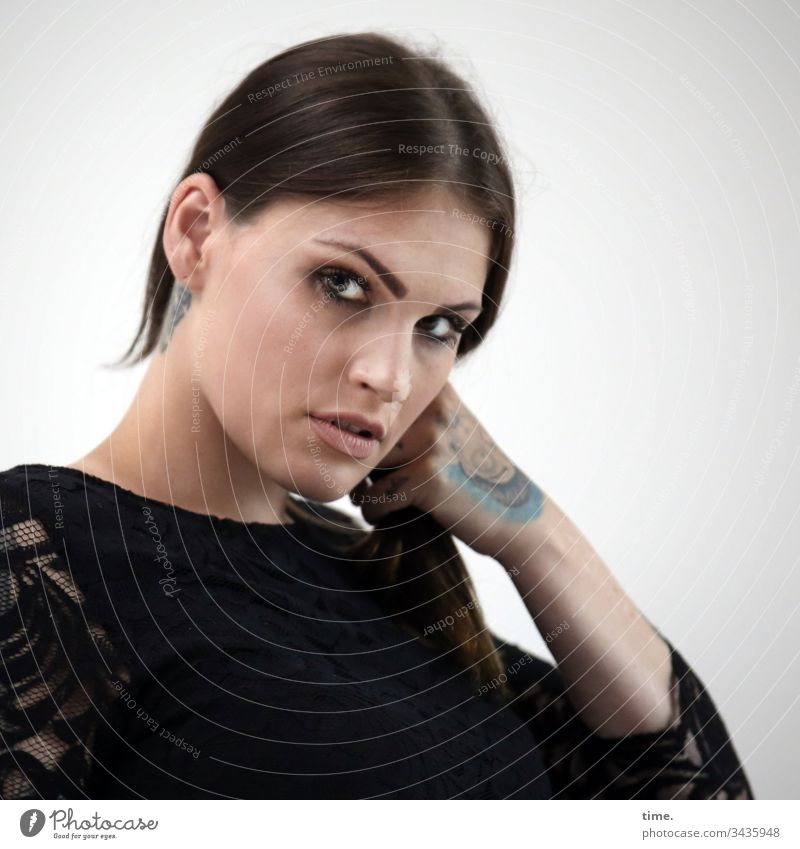 mixed emotions Woman Feminine feminine Skeptical Long-haired Braids Tattoo Dress Intensive portrait Looking Half-profile stop Isolated Image Wall (building)