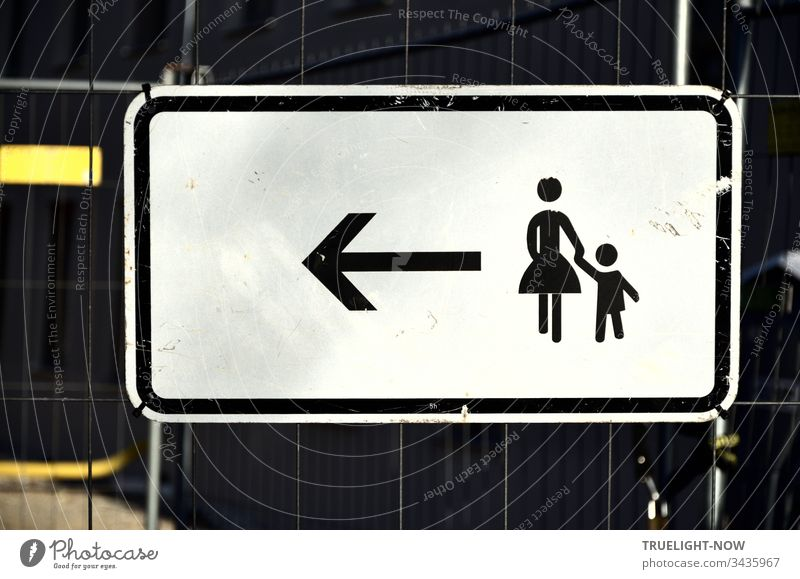 A white sign for pedestrians with a black pictogram on a barrier grille, signalled by an arrow to a stylised woman with a small child on her hand: Keep going left. | Corona Thoughts