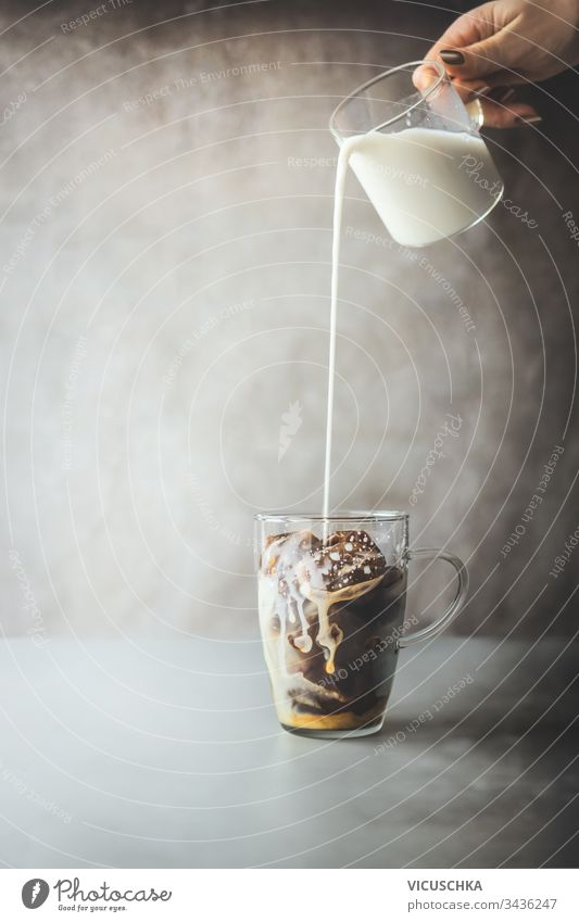 Ice coffee preparation. Female hand pouring cream milk in glass with coffee ice cubes on rustic table at concrete wall background. Iced coffee making. Summer refreshing beverage. Cold drink.